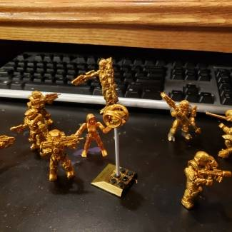 Image of: Golden heroes and villains battle at computer desk
