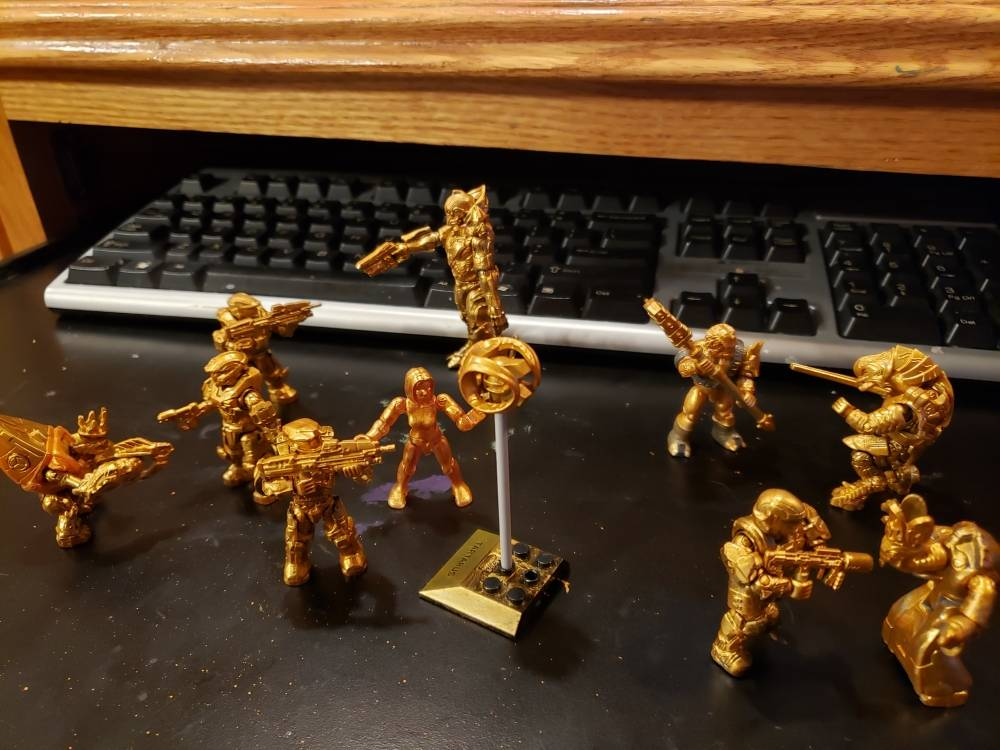 Golden heroes and villains battle at computer desk